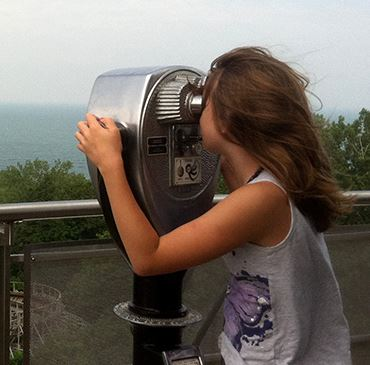 A young girl looking through a tower viewer atop a tall building